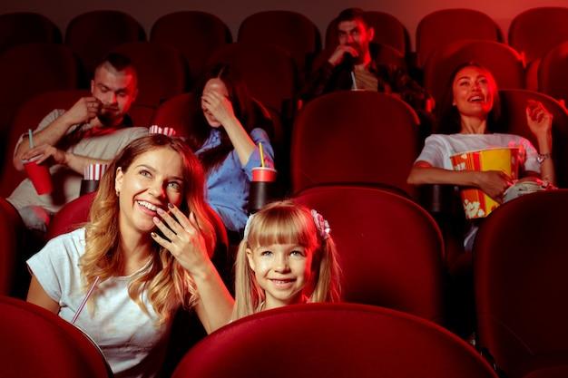 Grupa przyjaciół siedząc w kinie z popcornem i napojami
