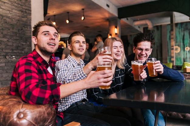 Grupa przyjaciół siedząc w restauracji barowej ciesząc się piwem