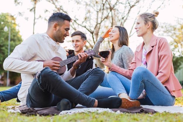 Grupa przyjaciół siedzących na trawie na świeżym powietrzu - młody mężczyzna grający na ukulele, podczas gdy jego przyjaciele cieszą się muzyką i dobrym winem.