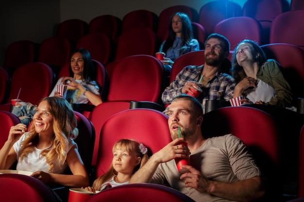 Grupa przyjaciół siedzących w kinie z popcornem i napojami