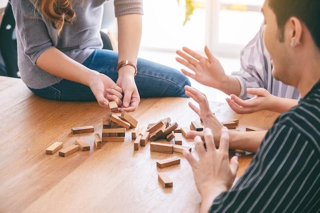 Grupa przyjaciół siedzi i gra w drewnianą grę tumble tower wraz z uczuciem szczęścia