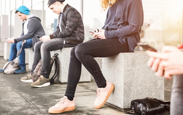 Grupa przyjaciół siedzi i używa smartphone przy uniwersyteckiej szkoły wyższa podwórka przerwą