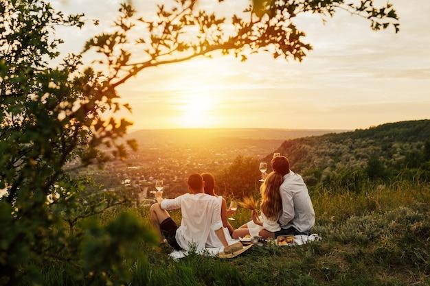 Grupa przyjaciół siedzi na górze i podziwiając niesamowity krajobraz i zachód słońca.