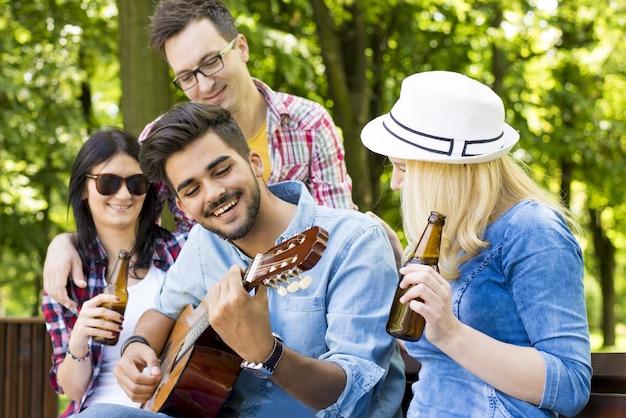 Grupa przyjaciół siedzi na ławce, gra na gitarze i ciesząc się czasem