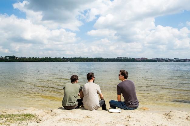 Grupa przyjaciół siedzi na piaszczystej plaży
