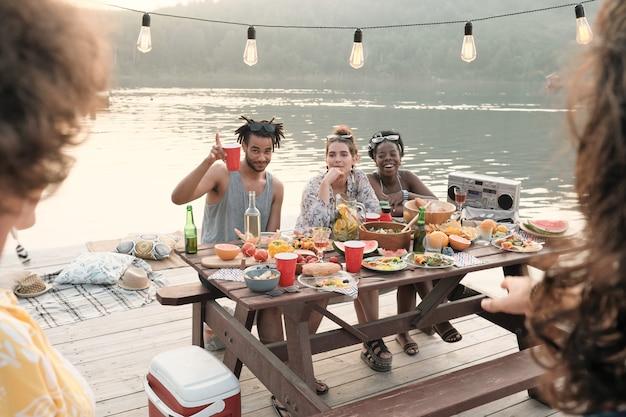 Grupa przyjaciół siedzi przy stole i jedzą piknik na świeżym powietrzu