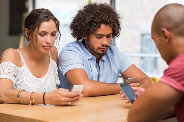 Grupa przyjaciół siedzi w kawiarni oddzielnie patrząc na swój telefon utrata komunikacji