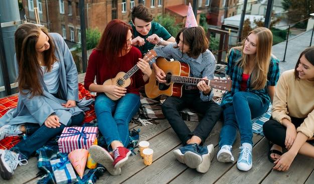 Grupa przyjaciół słucha ulicznych muzyków śpiewających i grających na gitarze i ukulele na imprezie na dachu. artystyczny styl życia muzyka. wypoczynek nastolatków