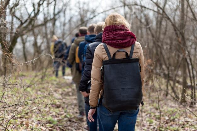 Grupa przyjaciół spaceru z plecakami w lesie wiosną od tyłu. turystów pieszych w lesie. koncepcja przygody, podróży, turystyki, aktywnego wypoczynku, wędrówek i przyjaźni.