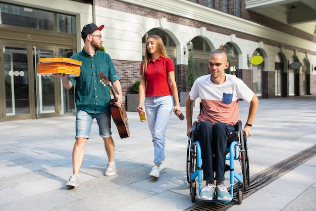 Grupa przyjaciół spacerująca ulicą miasta w letni dzień