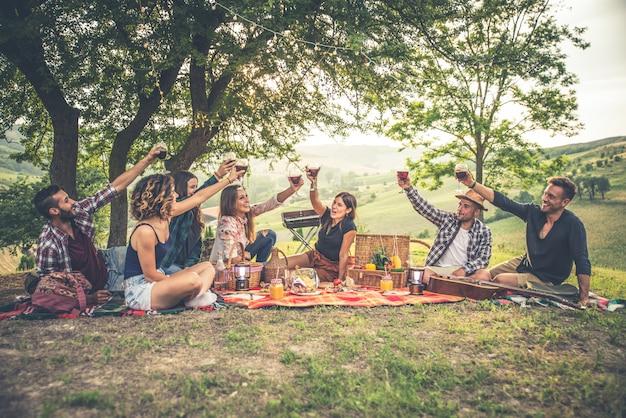 Grupa przyjaciół spędzających czas na pikniku i grillowaniu
