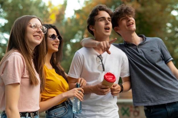 Grupa przyjaciół spędzających razem czas na świeżym powietrzu w parku