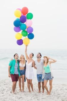 Grupa przyjaciół stoi na plaży z balonami