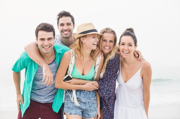Grupa przyjaciół stojących razem na plaży