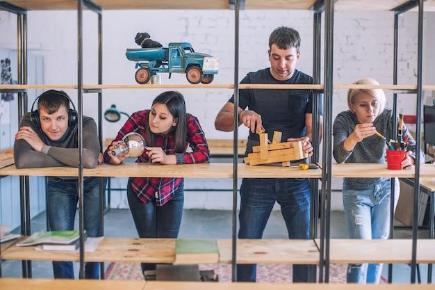 Grupa przyjaciół studentów robi i omawia kreatywne pomysły na strychu