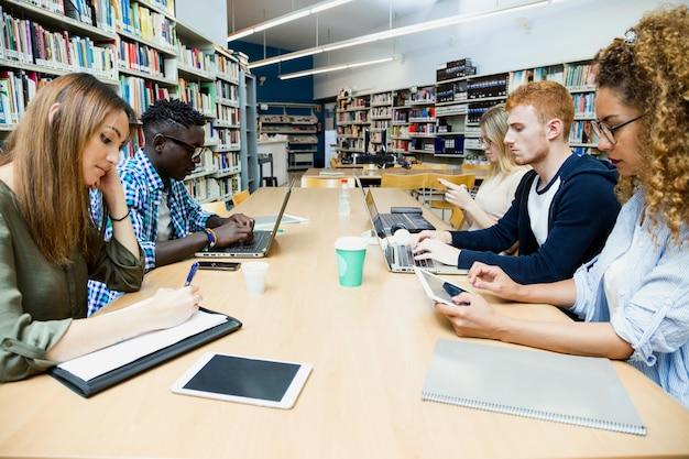 Grupa przyjaciół studiujących w bibliotece uniwersyteckiej.