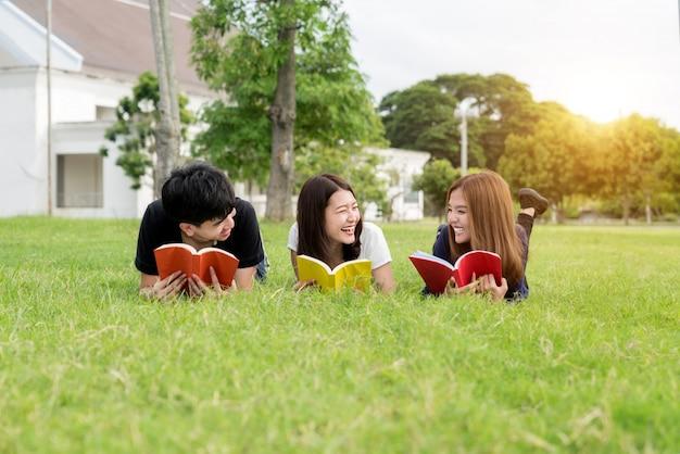 Grupa przyjaciół studiuje outdoors w parku przy szkołą.