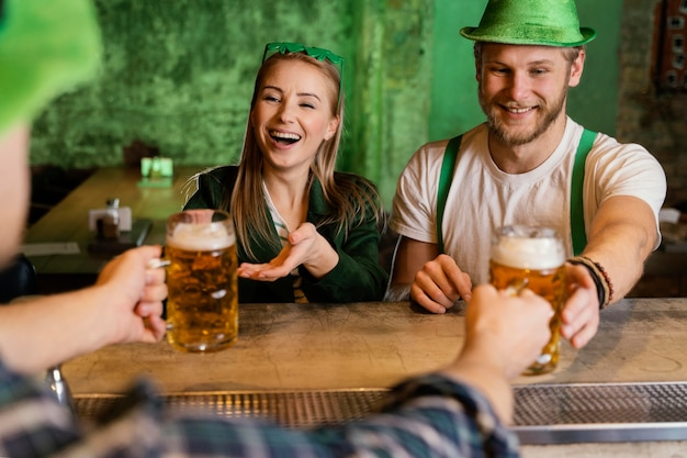 Grupa przyjaciół świętująca św. patrick's day z napojami
