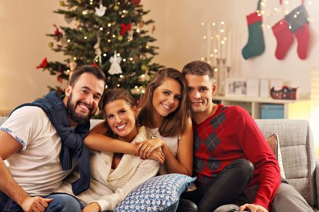 Grupa przyjaciół świętujących boże narodzenie w domu