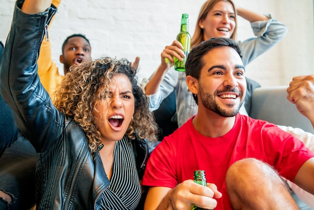 Grupa przyjaciół świętujących i dopingujących podczas wspólnego oglądania meczu. koncepcja przyjaciół.
