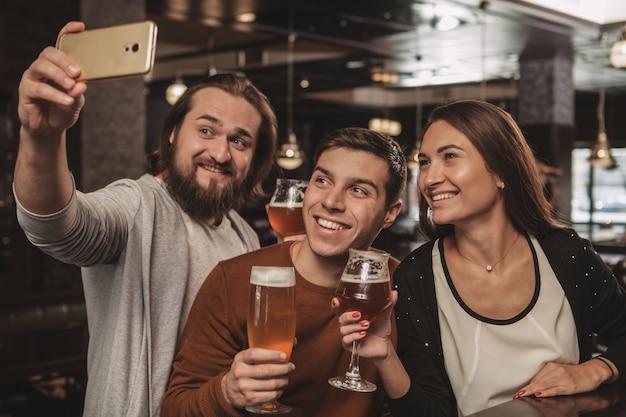 Grupa przyjaciół świętuje w pubie, pijąc piwo razem