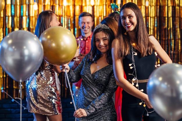 Grupa przyjaciół świętuje z fajerwerkami i okularami, ciesząc się christmas party