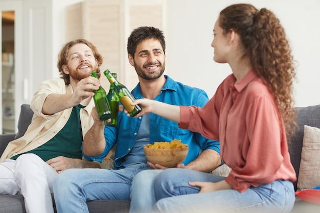 Grupa przyjaciół szczęk butelek piwa podczas oglądania telewizji razem, siedząc na wygodnej kanapie w domu