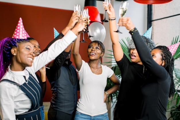 Grupa przyjaciół szczęśliwy afrykańskich picia szampana i świętować nowy rok. sylwestrowa impreza. przyjęcie urodzinowe