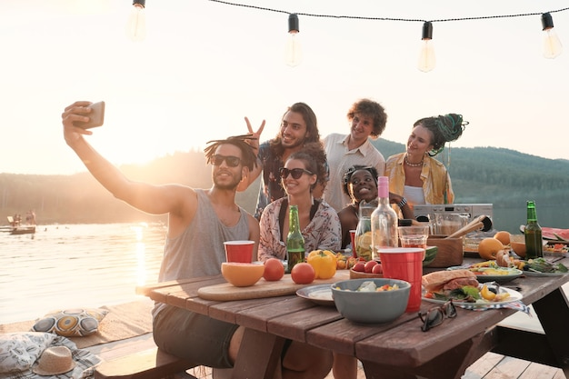 Grupa przyjaciół szczęśliwy co selfie na telefon komórkowy siedząc przy stole podczas obiadu na świeżym powietrzu