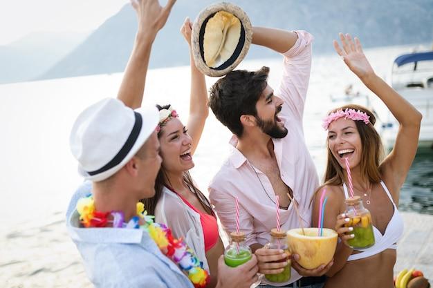 Grupa przyjaciół szczęśliwy zabawy na plaży party picia koktajl o zachodzie słońca. koncepcja letniej radości i przyjaźni z młodymi ludźmi na wakacjach