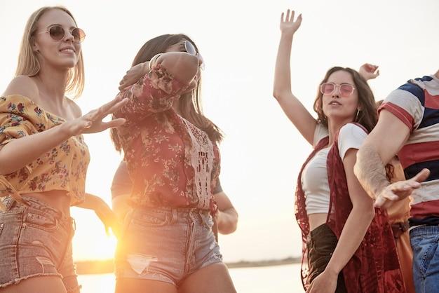 Grupa przyjaciół tańczących na świeżym powietrzu