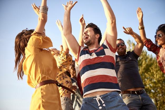 Grupa przyjaciół tańczących w słoneczny dzień na świeżym powietrzu