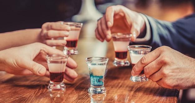 Grupa przyjaciół tequila strzelała kieliszkami w barze. męskie ręce szklanki shot lub likieru. przyjaciele piją shota lub likier. pięć szklanek alkoholu.