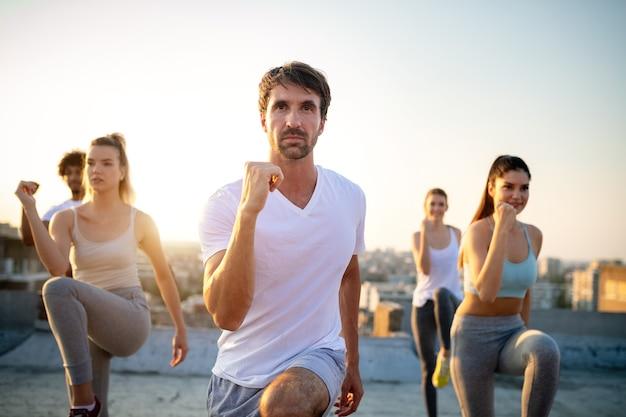 Grupa przyjaciół trenuje fitness razem na świeżym powietrzu, żyjąc aktywnie i zdrowo