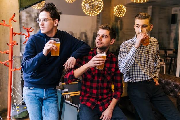 Grupa przyjaciół, trzymając szklanki piwa patrząc od hotelu