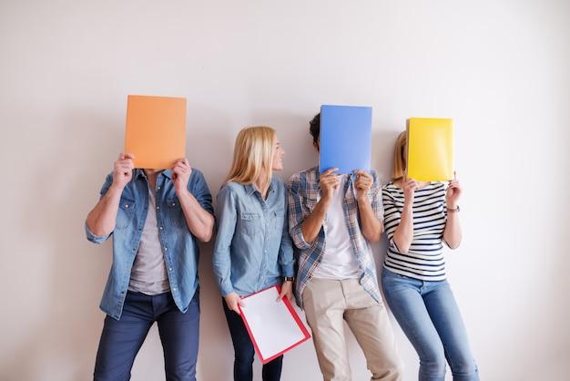 Grupa przyjaciół trzymających foldery przed twarzą
