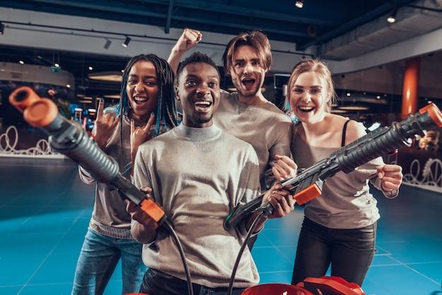 Grupa przyjaciół w arcade. facet z bronią.