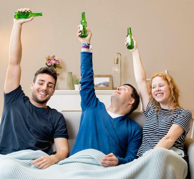 Grupa przyjaciół w domu wiwatują z piwem