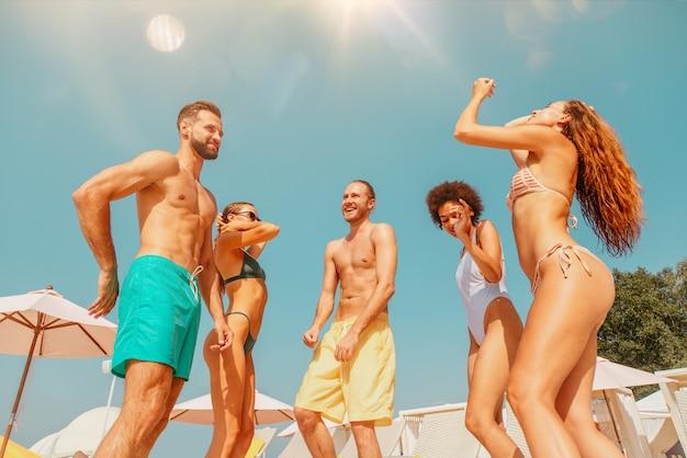 Grupa przyjaciół w muzyce tanecznej w stroju kąpielowym na basenie