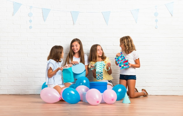 Grupa przyjaciół w przyjęciu urodzinowym, otwierając prezenty