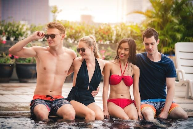 Grupa przyjaciół w strój kąpielowy i bikini cieszyć się siedzi na poolside w wakacje w lecie