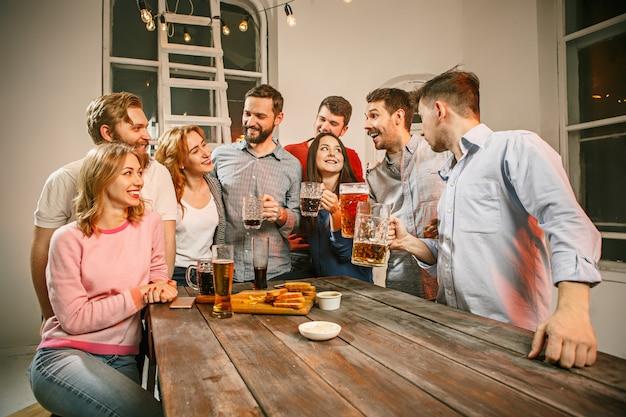 Grupa przyjaciół wieczorem drinki z piwem na drewnianym stole