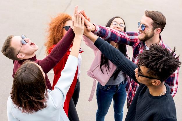 Grupa przyjaciół wieloetnicznych dając wysoko na ulicy
