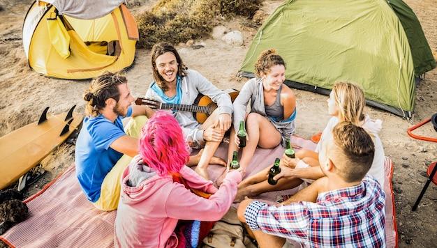 Grupa przyjaciół, wspólna zabawa na kempingu na plaży - koncepcja podróży szczęśliwej przyjaźni z młodymi podróżnikami grającymi na gitarze i pijącymi butelkowane piwo na letnim obozie surfingowym