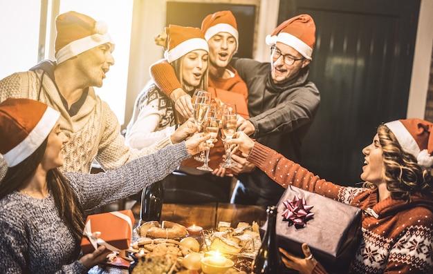 Grupa przyjaciół z czapkami mikołaja wymieniającymi prezenty świąteczne z grzanką z szampana i winem podczas domowej kolacji