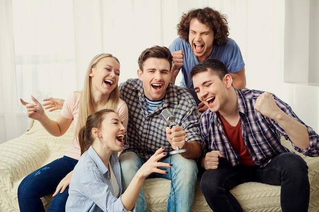 Grupa przyjaciół z mikrofonem śpiewa zabawne piosenki na imprezie w pomieszczeniu.
