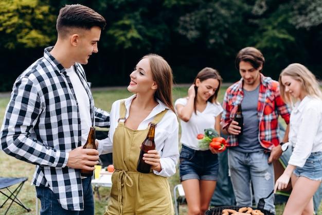 Grupa przyjaciół z napojami i jedzeniem miło spędza czas na kempingu. - wizerunek