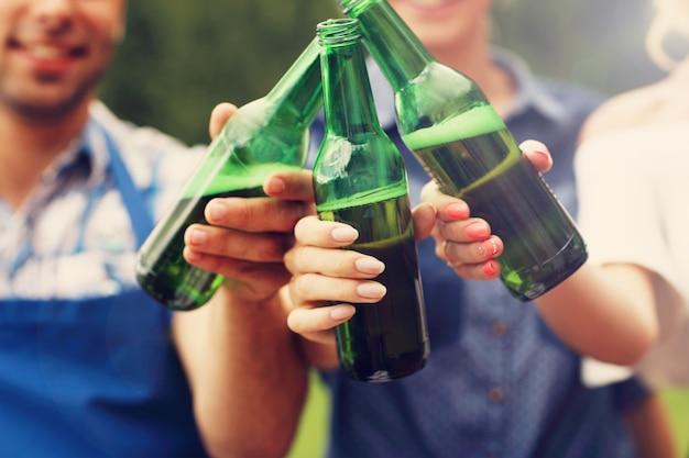 Grupa przyjaciół z piwem podczas imprezy przy grillu