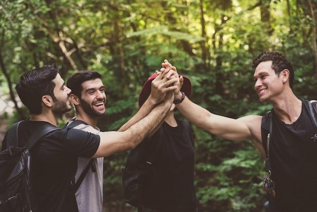 Grupa przyjaciół z plecakami wesołej zabawy łączy ręce podczas spaceru przygody w lesie
