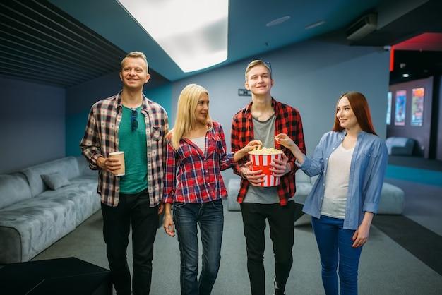Grupa przyjaciół z popcornem stoi przed seansem w sali kinowej. młodzież płci męskiej i żeńskiej w kinie